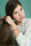 Teen girl with long stright thick brown hair. Teen pretty girl with long stright thick brown hair make pony tail close up photo Royalty Free Stock Photo