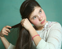 Teen girl with long stright thick brown hair. Teen pretty girl with long stright thick brown hair make pony tail close up photo Stock Image