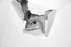 Teen girl look from hole in white paper. Black and white filter Stock Photography