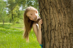 Teen girl look out from the tree in park Stock Image