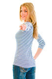 Teen girl looking back and pointing finger at you Royalty Free Stock Photo