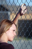 Teen girl looking through fence Stock Images