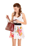 Teen girl looking in her purse Stock Images