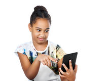 Teen girl looking at the screen of the tablet. Dark-skinned girl has fun pointing Stock Photos