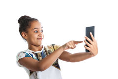 teen girl looking at the screen of the tablet. Dark-skinned girl has fun pointing Royalty Free Stock Photography