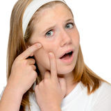 Teen girl looking skin spotted pimple squeezing Stock Photography