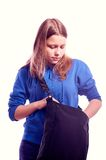 Teen girl looking for something in a bag. Sad dissapointed teen girl looking for something in a bag Stock Images