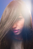 Teen girl looking from under hair on lens flare Royalty Free Stock Image