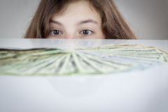Teen girl looking at US dollars Royalty Free Stock Images