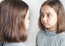 Teen girl looks at her reflection in the mirror. A teenage girl in a gray jacket looks at her reflection in the mirror royalty free stock image