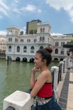 Teen girl looks left, macau waterfront, china, ocean and blue sky outdoors few clouds. A young asian teen girl looks left across the Macau waterfront area with royalty free stock photo