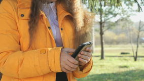 Teen girl looks photos using a mobile phone. Teen girl standing in nature park holds a mobile phone looks photos her friend girl in social networks stock video