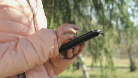Teen girl looks photos using a mobile phone. Teen girl standing in nature park holds a mobile phone looks photos her friend girl in social networks stock video footage