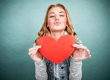 Teen girl in love. Portrait of cute teen girl with red paper heart  on gray background, kiss with love, Valentine day, affection concept Stock Image