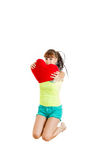 Teen girl in love jumping of joy holding red heart. Wearing shorts barefoot Royalty Free Stock Photography