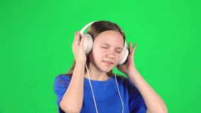 Teen girl listens to music and moving in large white headphones on green background. Slow motion. Teen girl with a lovely smile listens to music and moving in stock footage