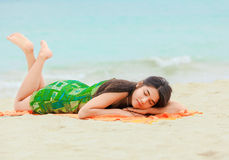 Teen girl lying down on Hawaiian beach, resting by ocean Royalty Free Stock Photography