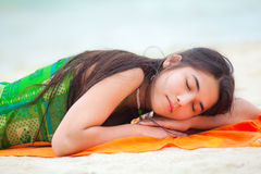 Teen girl lying down on Hawaiian beach, resting by ocean Stock Images