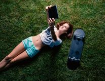 Teen girl lying down the park grass and make selfie with her skateboard lying near top view stock image