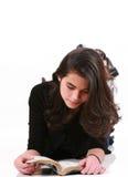 Teen girl lying on floor reading Bible stock photos