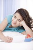 Teen girl lying on floor writing a letter or note Royalty Free Stock Photos