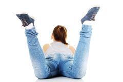 Teen girl lying on her tummy. Back view of teen girl lying on her tummy on white background Royalty Free Stock Photo