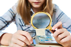 Teen girl with magnifier looks his stamp collection Royalty Free Stock Image