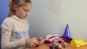 Teen girl makes out of colored foil miniature gifts. In the form of a square to decorate Christmas tree stock video