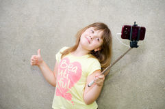 Teen girl makes selfie. On smartphone with monopod in hands Royalty Free Stock Image