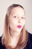 Teen girl making cute faces. Happy teen girl making cute faces with pomade on lips Stock Photos