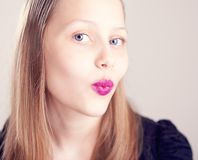 Teen girl making cute faces. Happy teen girl making cute faces with pomade on lips Stock Images