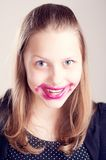 Teen girl making funny faces. Happy teen girl making funny faces with pomade on lips and cheeks Royalty Free Stock Photography