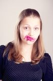 Teen girl making funny faces. Happy teen girl making funny faces with pomade on lips and cheeks Stock Image