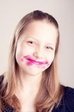 Teen girl making funny faces. Happy teen girl making funny faces with pomade on lips and cheeks Stock Photos