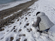 Teen girl making snowman on winter beach royalty free stock photo
