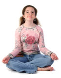 Teen Girl Meditating. A teenaged girl with her legs crossed and palms extended in meditation. Isolated royalty free stock photo