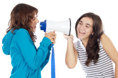 Teen girl with megaphone. Shouting to another girl Stock Photo