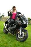 Teen Girl on Motorbike. Young woman on a black motorcycle royalty free stock images