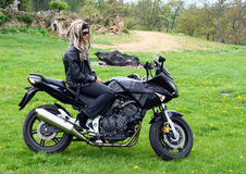 Teen girl on motorbike. Young woman on a black motorcycle royalty free stock photos
