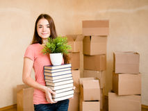 Teen girl moving house to college, holding pile books and plant Stock Photos