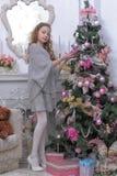 Teen girl near the Christmas tree Stock Image