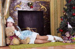 Teen girl near fireplace with teddy bear. Nice teen girl in Snow-maiden costume lying near fireplace with teddy bear stock photo