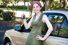 Teen Girl with New Car. Pretty teen girl leaning on her new car and holding car keys Royalty Free Stock Photo