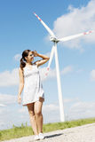 Teen girl next to wind turbine. Royalty Free Stock Photo