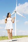 Teen girl next to wind turbine. Royalty Free Stock Photos