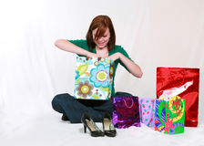 Teen girl opening gift bag. Redhead teen girl with shopping bags and shoes Royalty Free Stock Photo