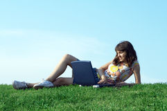 Teen girl in outdoor study. With a laptop Royalty Free Stock Photo