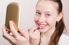 Teen girl paints lips with lipstick Royalty Free Stock Photo