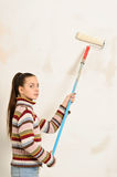 Teen girl paints the wall Stock Image