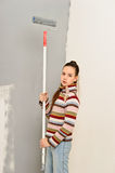 Teen girl paints the wall Royalty Free Stock Image